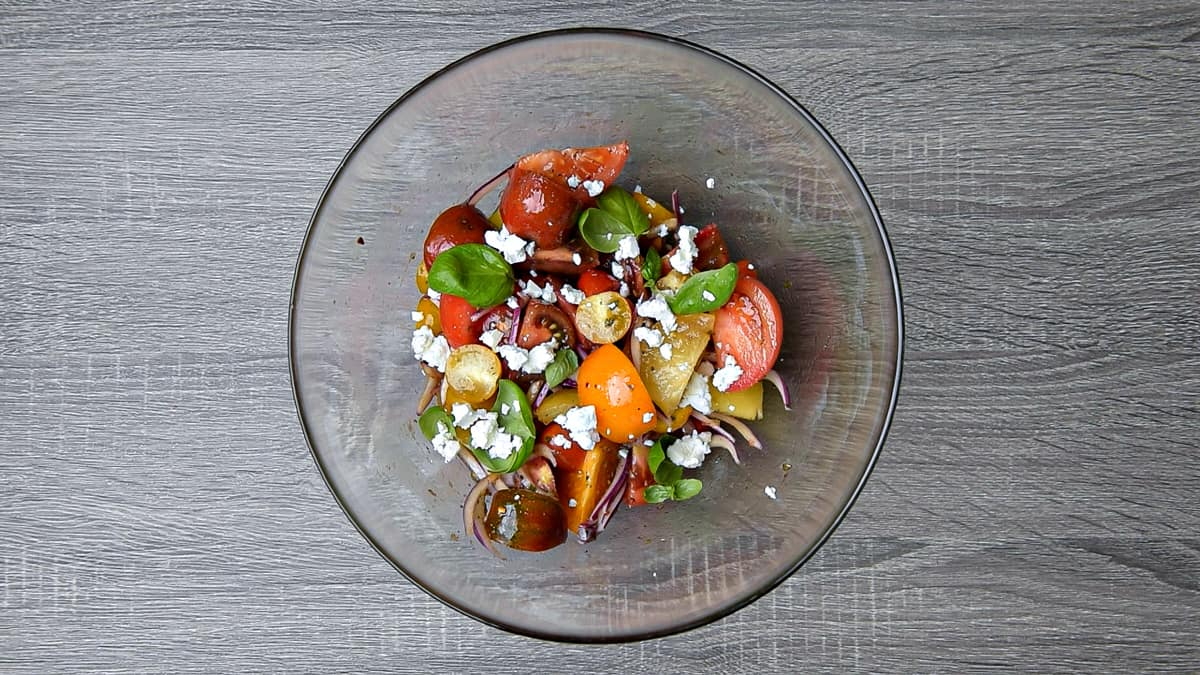 basil and feta added to tomato salad after resting for 15 minutes