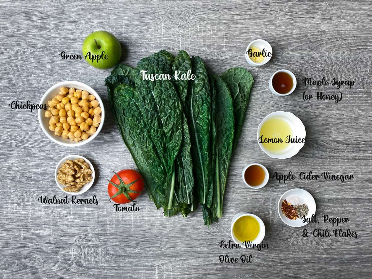 ingredients for kale apple salad with maple apple cider vinaigrette laid out on a grey table