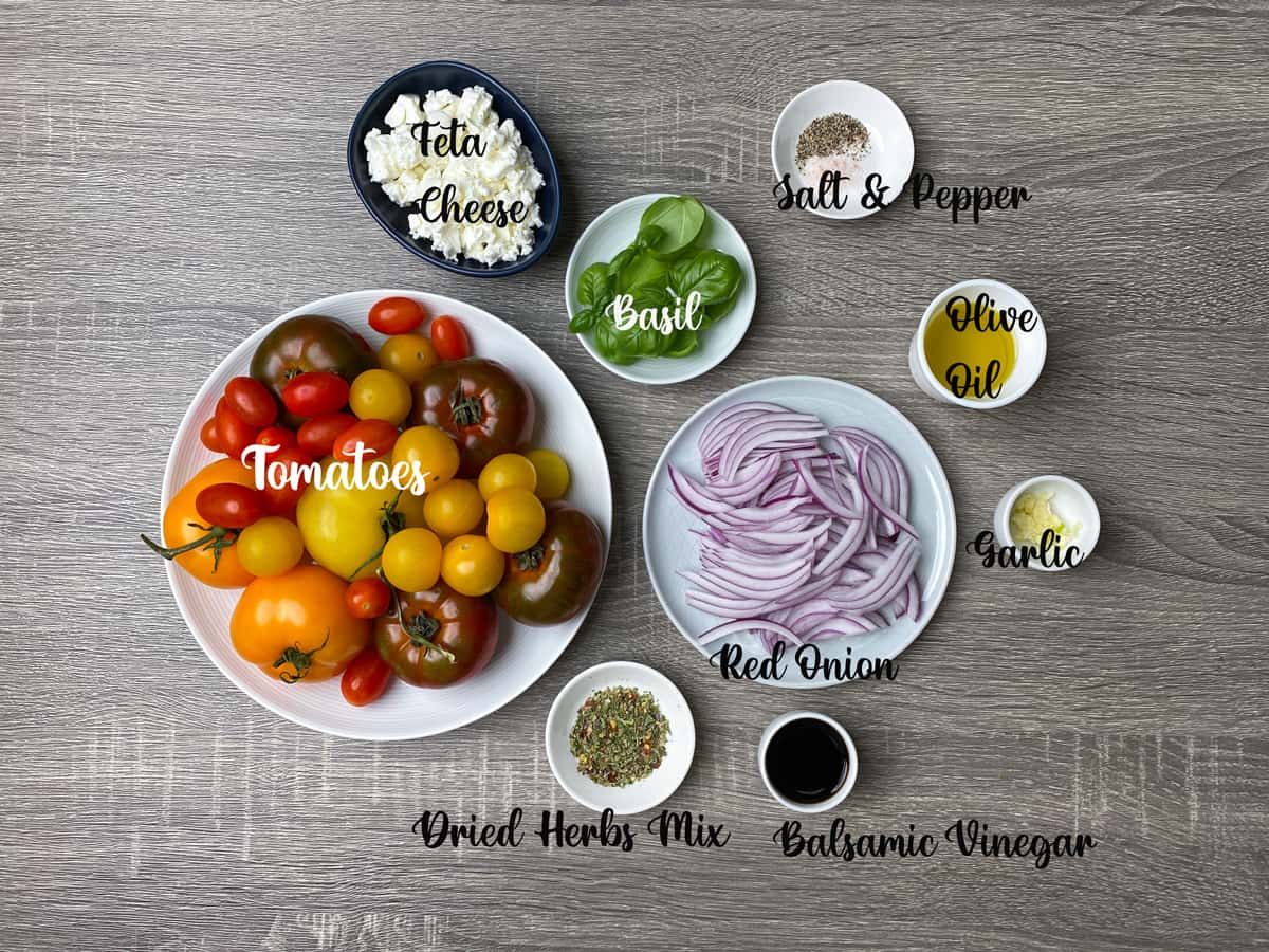 ingredients for garden fresh tomato salad laid out on a wooden table