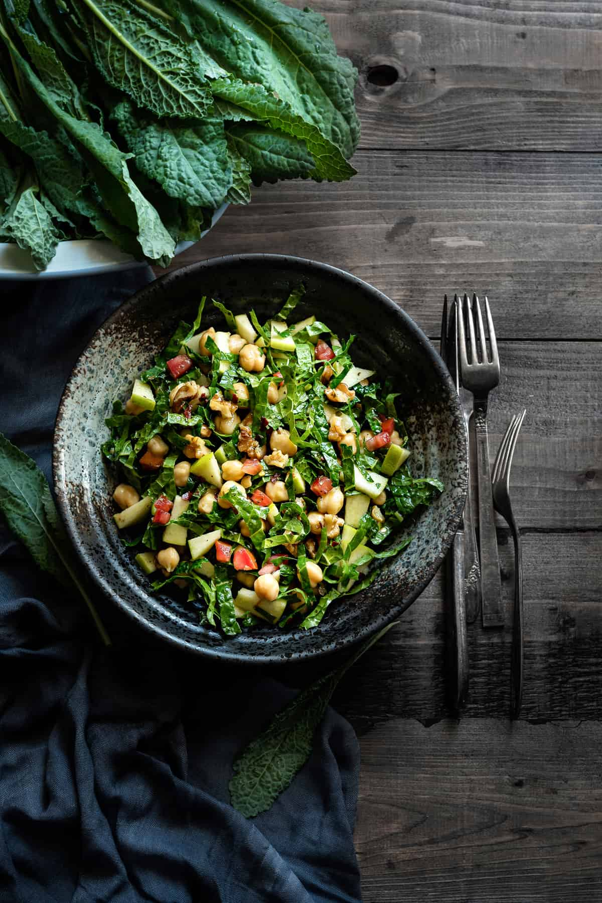 overhead shot of a bowl of tuscan kale and apple salad with walnuts, chickpeas and tomatoes