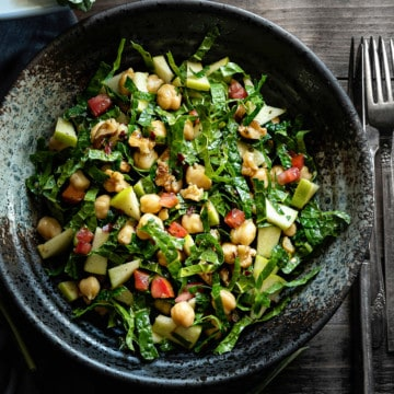 kale apple salad in a grey speckled bowl on a grey table with silverware to the side