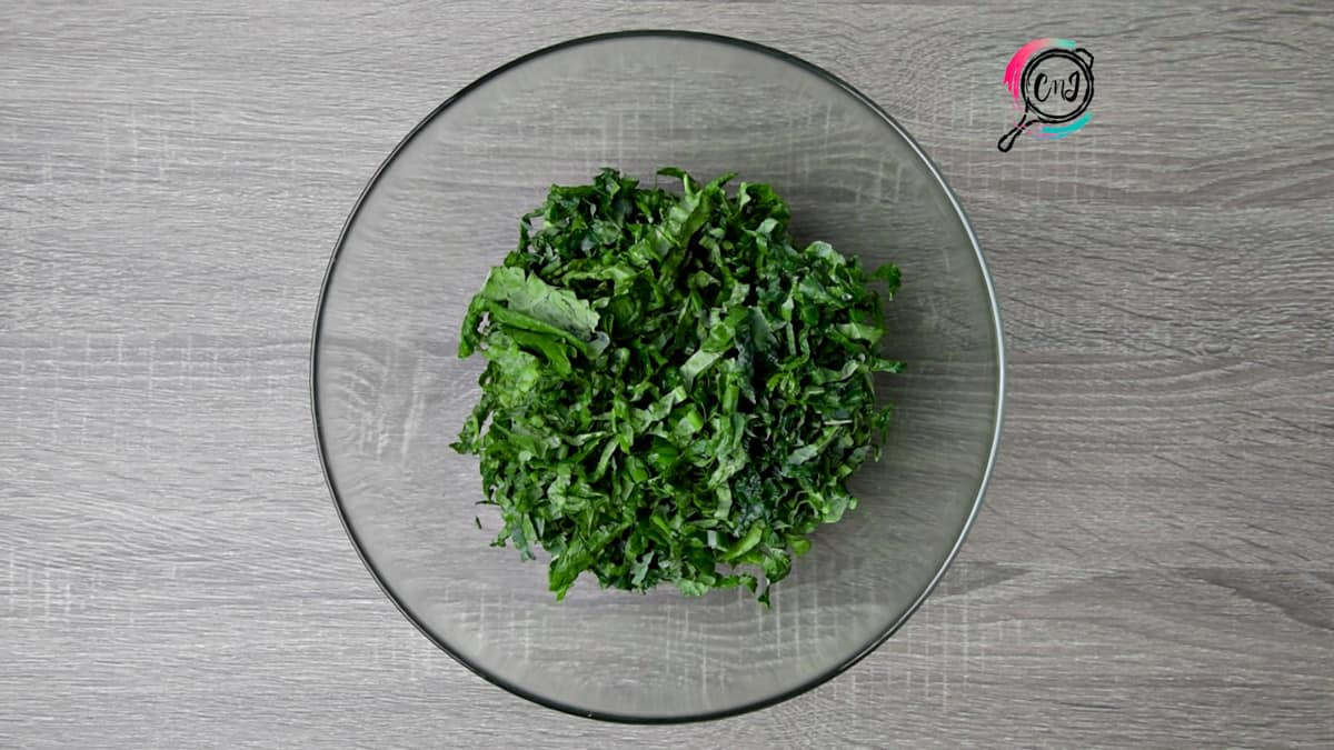 ribbons of kale in a clear glass mixing bowl on a grey table