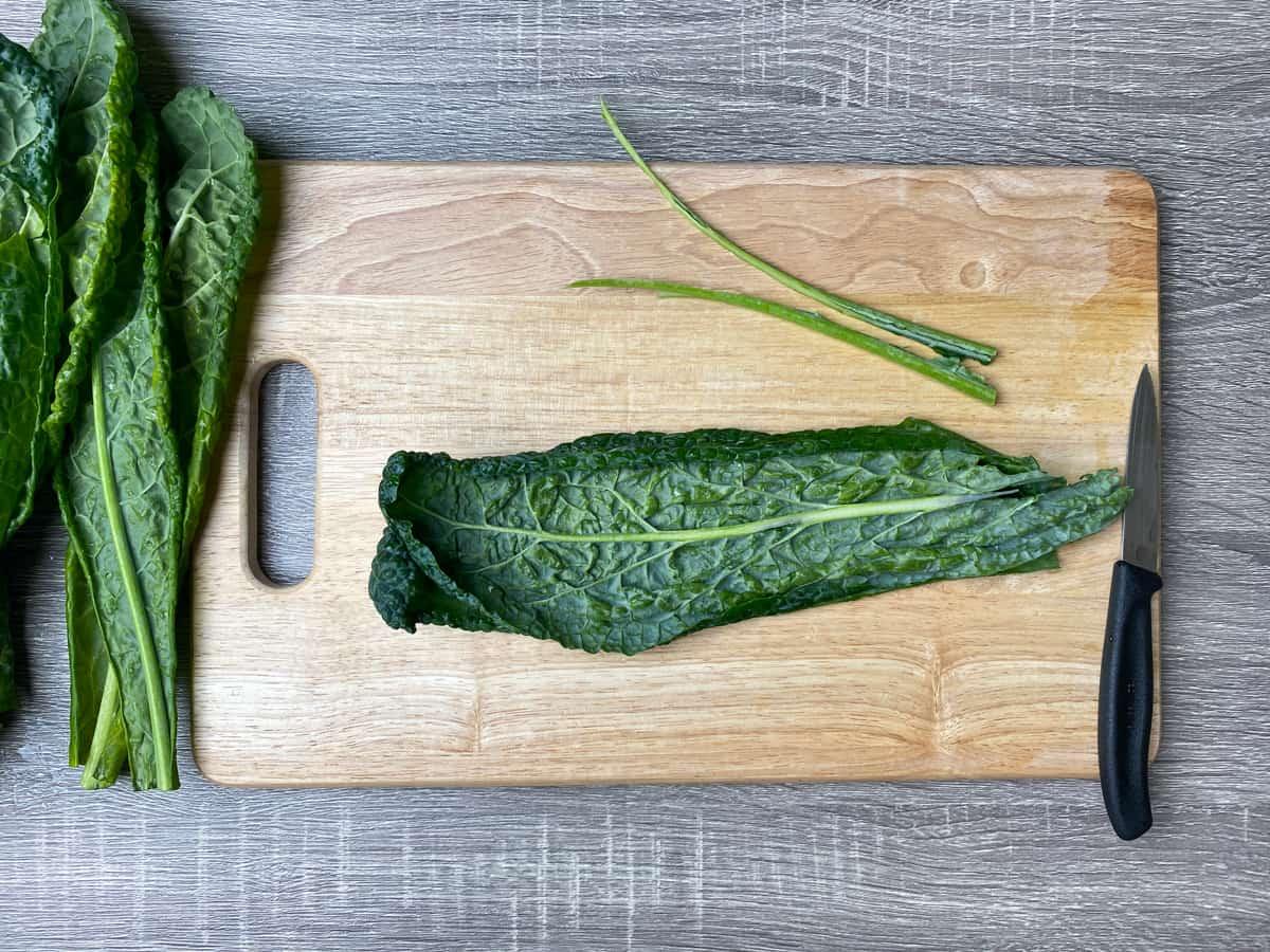 removing stems from lacinato kale on a wooden cutting board