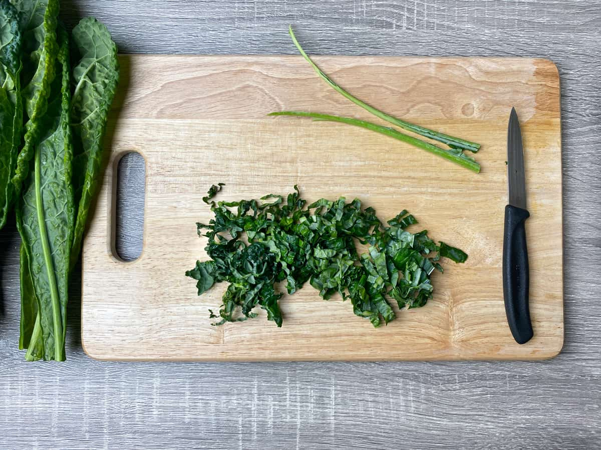 kale leaf sliced into ribbons on a wooden cutting board