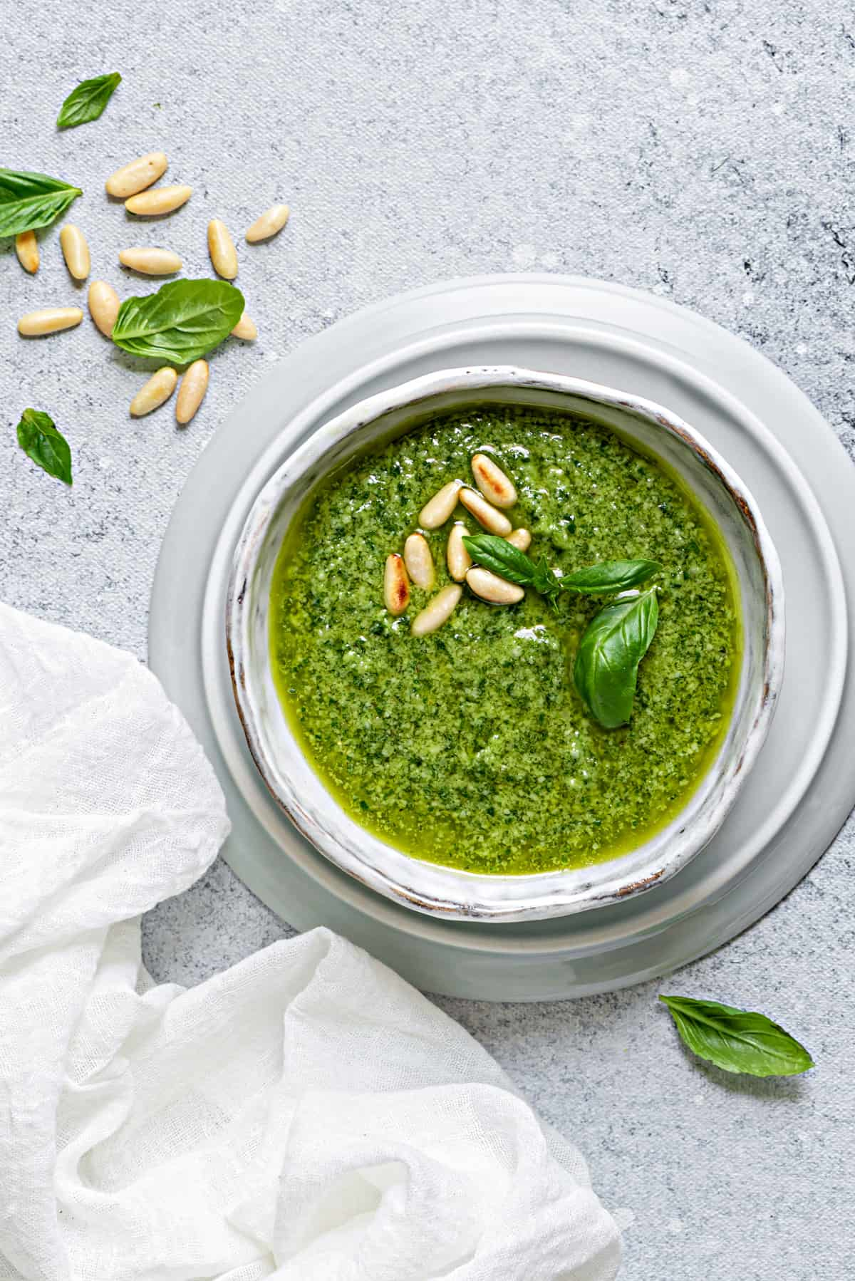 basil pesto in a serving dish on a grey table with a scattering of toasted pine nuts