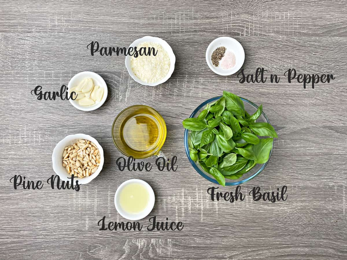 ingredients for basil pesto sauce placed in glass bowls and kept on a grey wooden table
