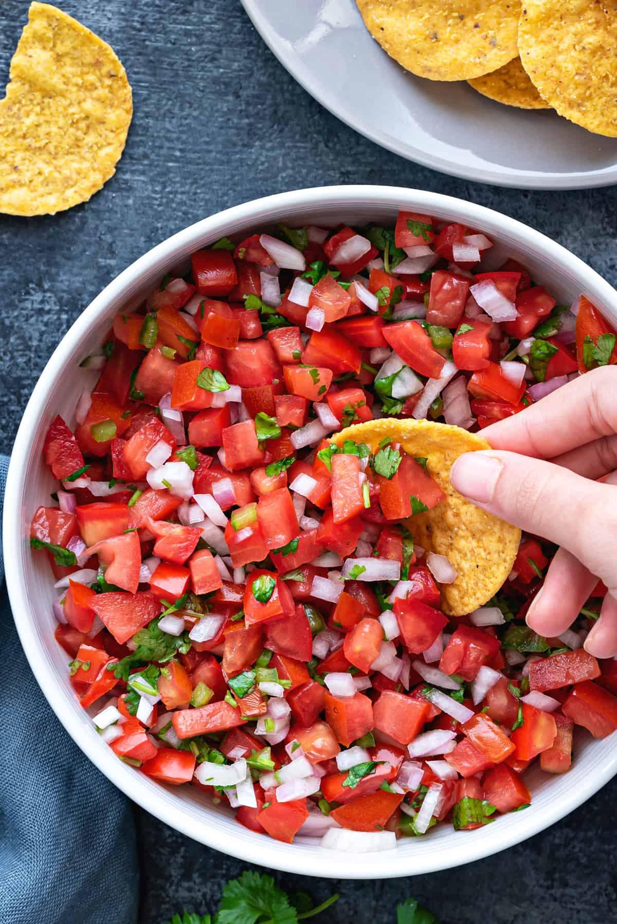 hand dipping a round tortilla chip into a white bowl of pico de gallo salsa fresca
