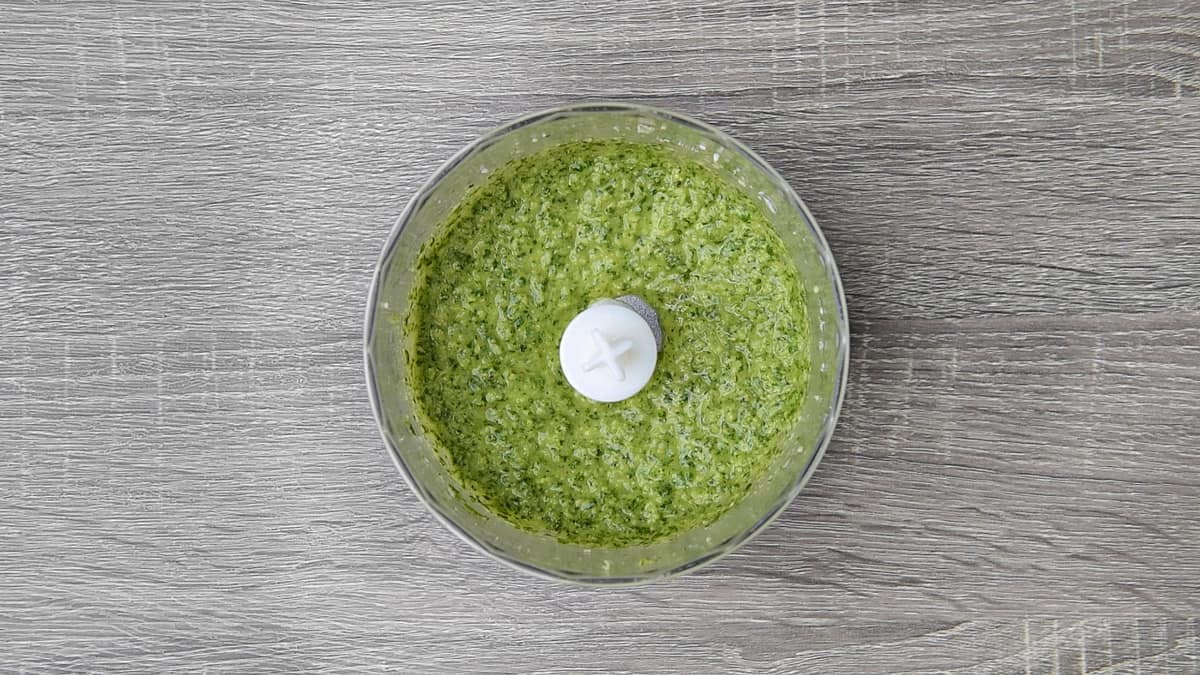 finished basil pesto sauce in the bowl of a immersion blender chopper bowl