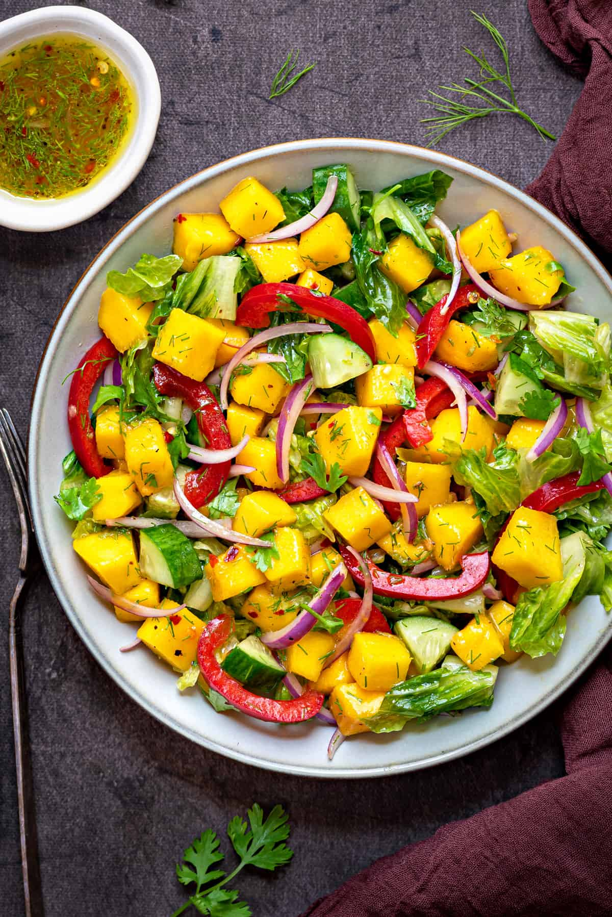 close up overhead shot of white bowl filled with fresh mango salad on a grey table