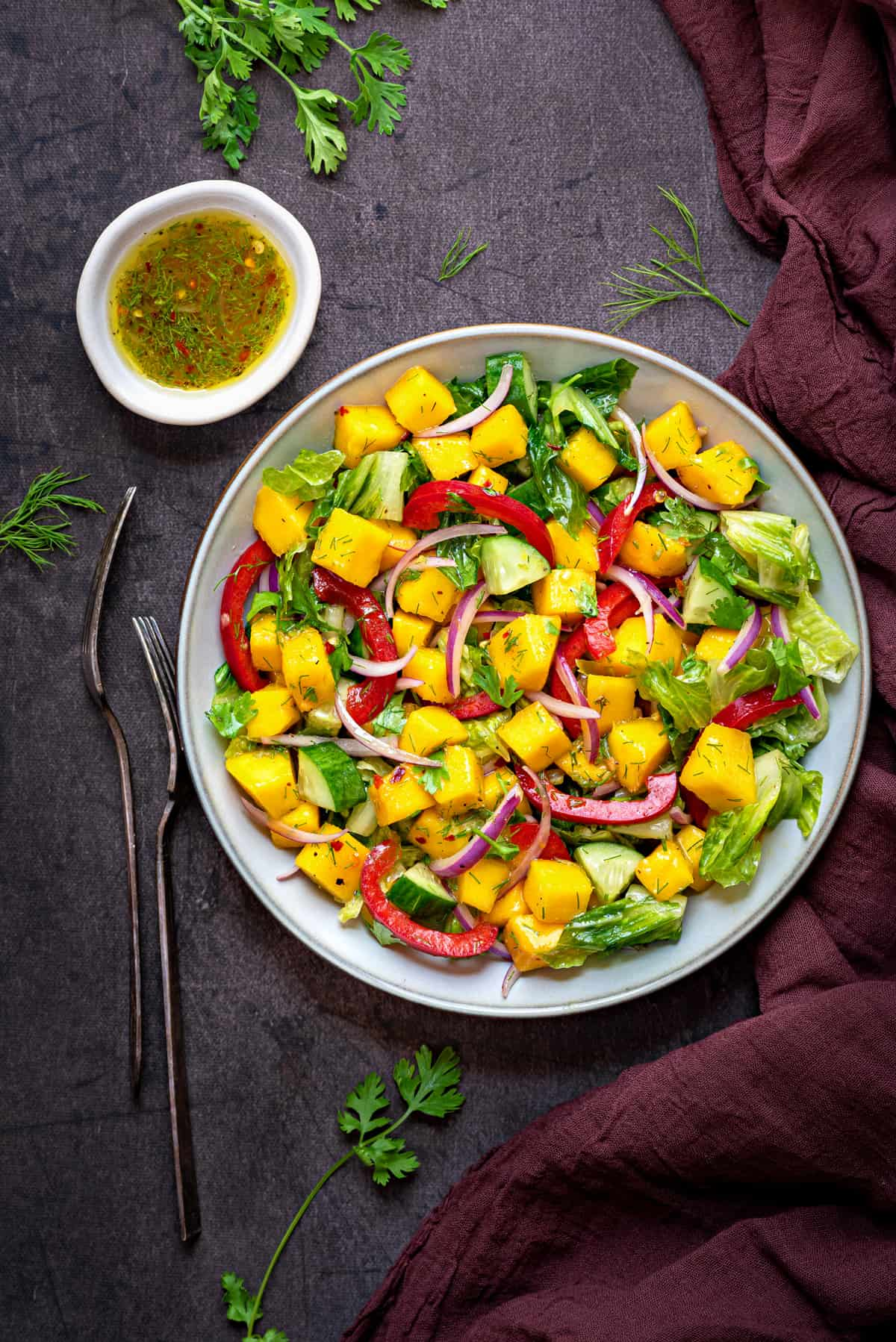 mango salad in a grey bowl with two forks and dressing in bowl kept on side