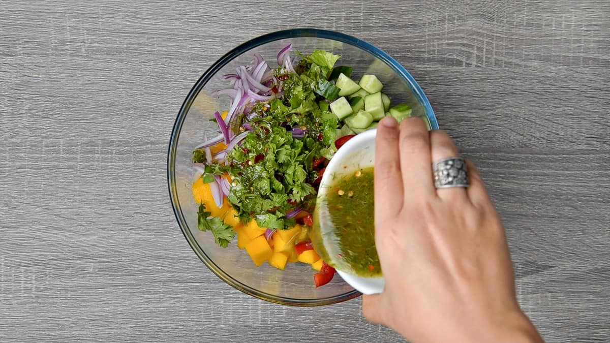 salad dressing being poured over veggies and mango