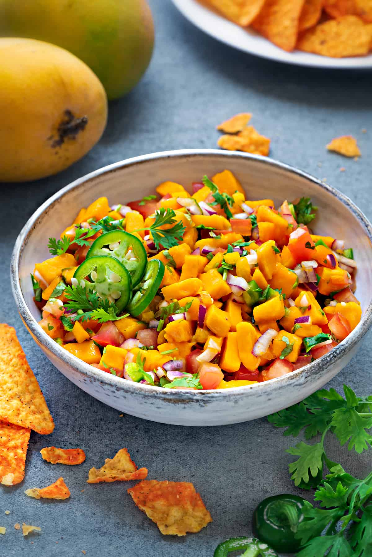 mango salsa in a white earthenware bowl next to a plate of tortilla chips and mangoes