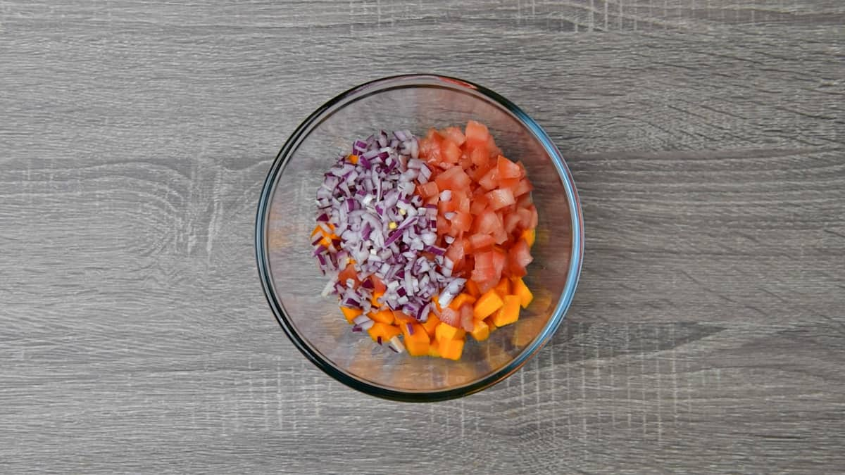 chopped tomatoes and onions added to bowl with mango