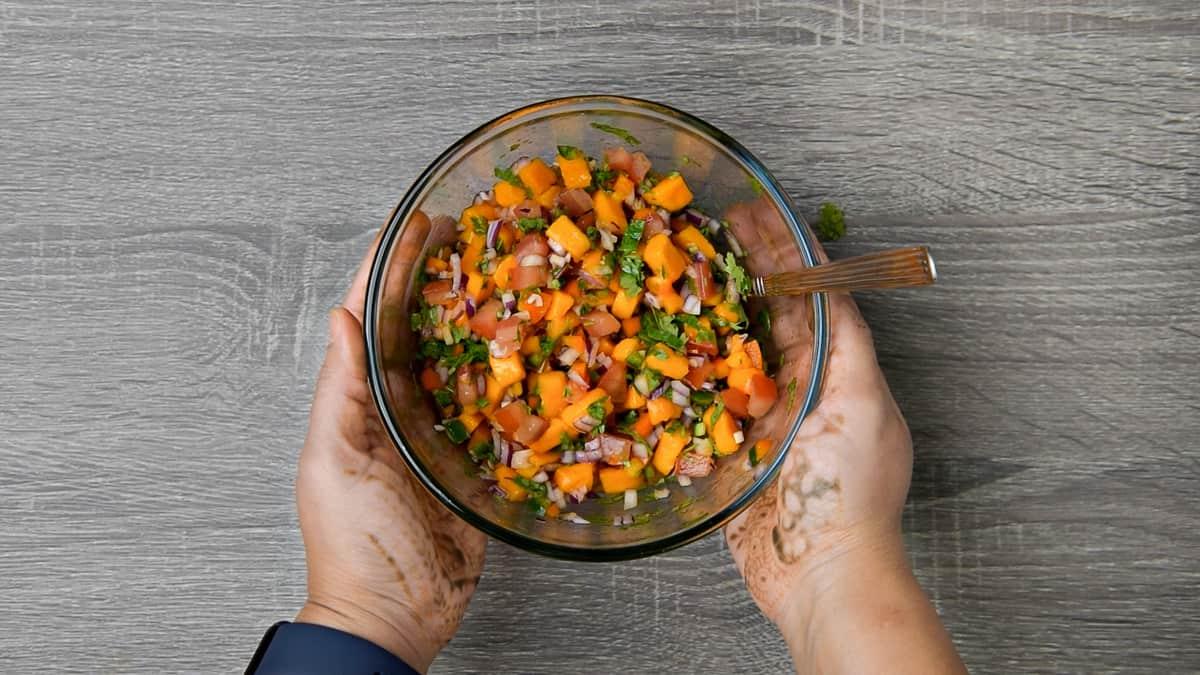 hands holding bowl of mango salsa after tossing ingredients together