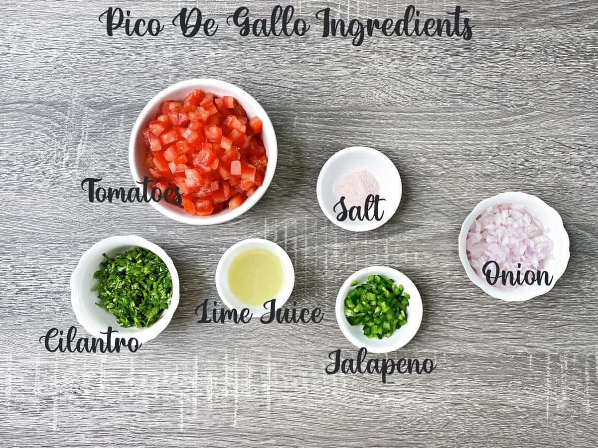 ingredients for making pico de gallo measured out in white bowls on a grey table