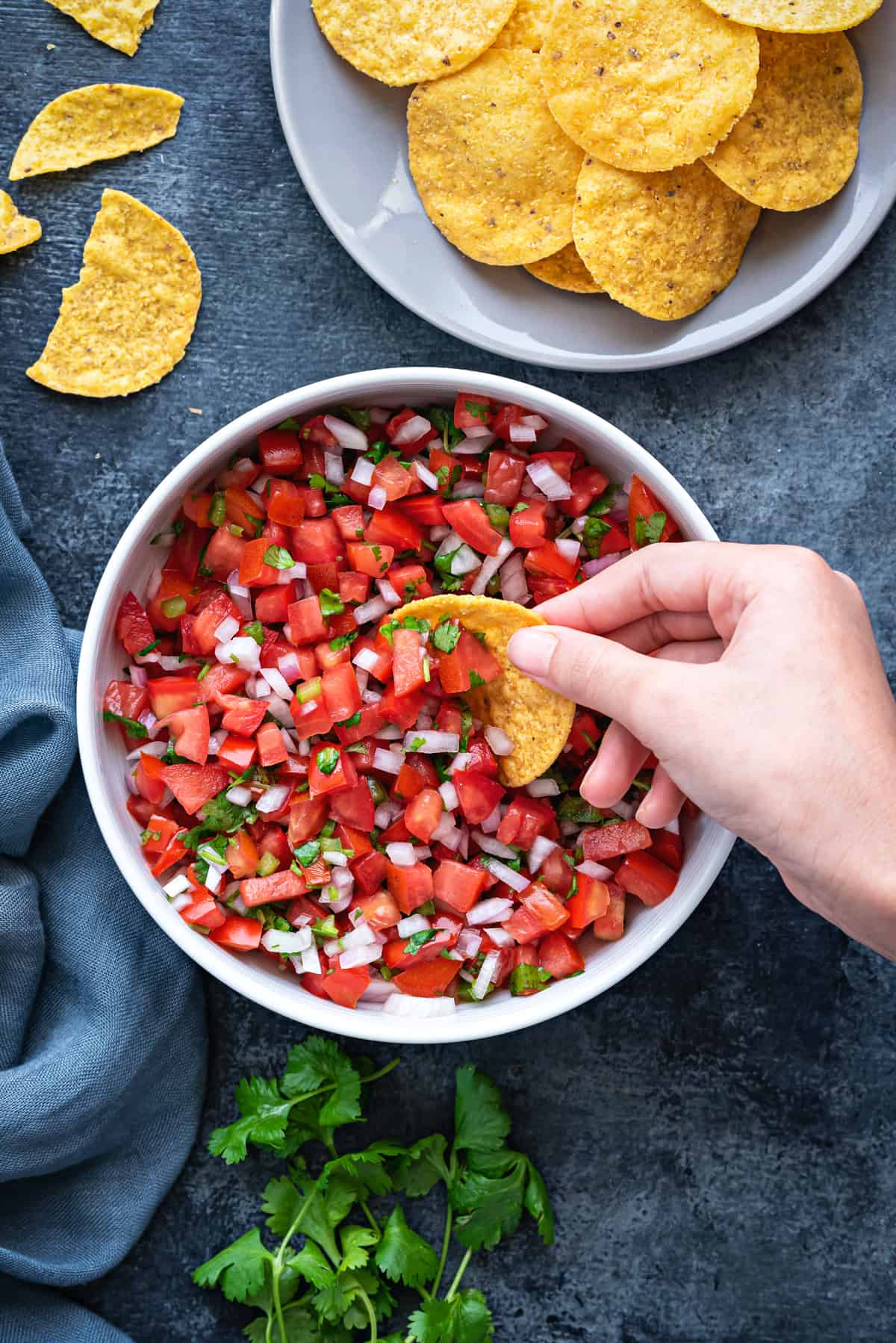 white bowl of pico de gallo salsa on a table with a bowl of tortilla chips
