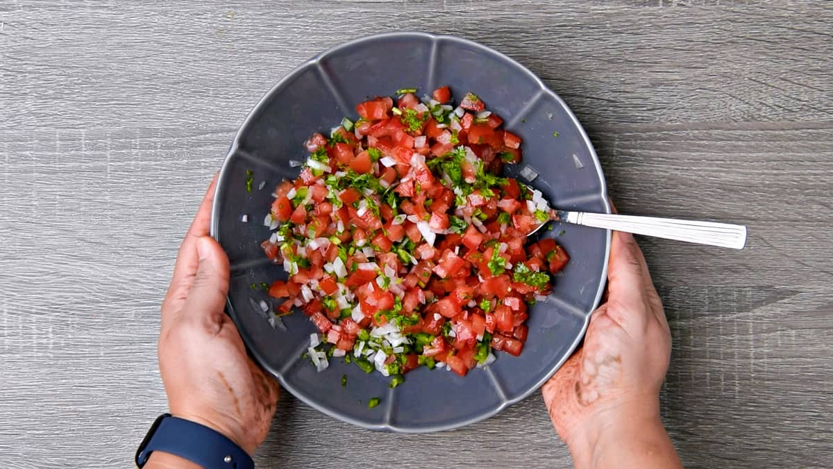 hands holding bowl of salsa after mixing