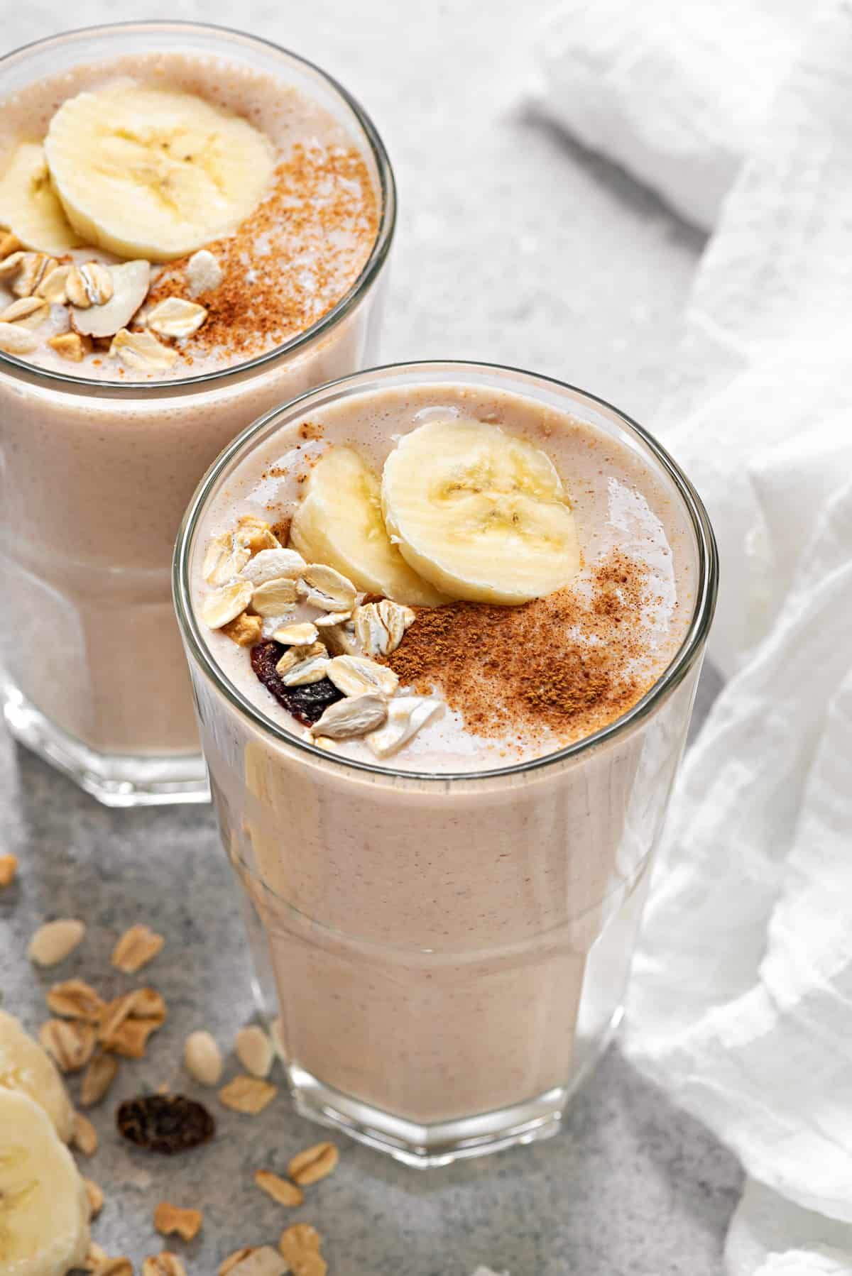 healthy banana breakfast smoothies topped with sliced banana, muesli and dusted with cinnamon