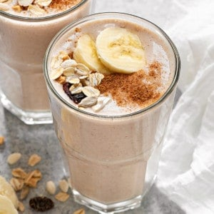 healthy muesli banana breakfast smoothies topped with sliced banana, muesli and dusted with cinnamon