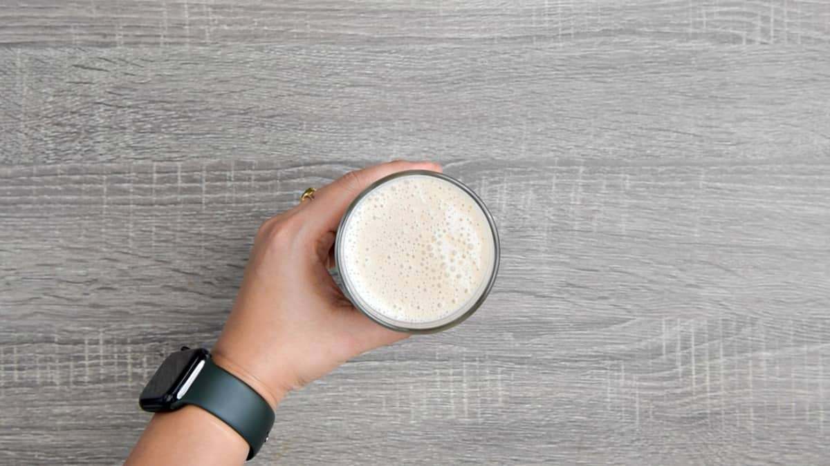 hand holding glass of banana breakfast smoothie