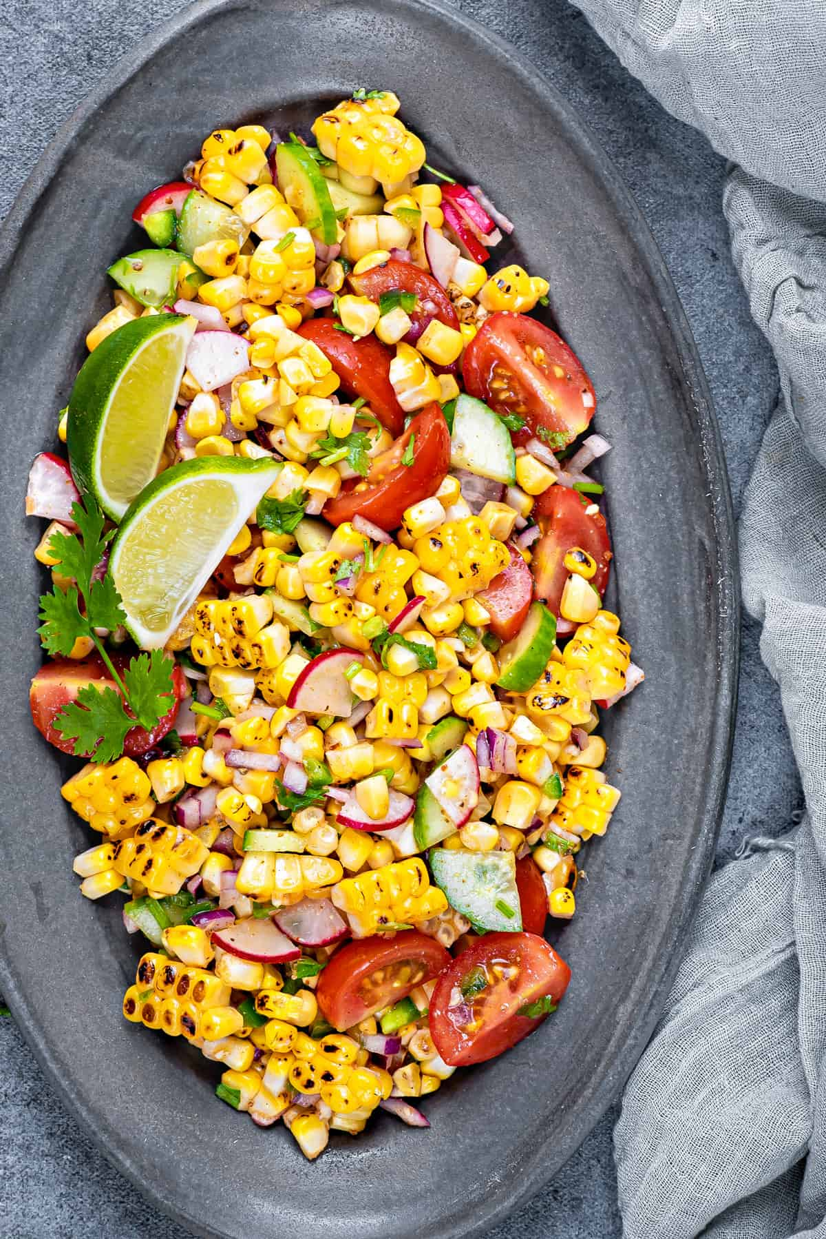 Serving plate loaded up with fresh summer corn salad garnished with lime wedges and fresh cilantro