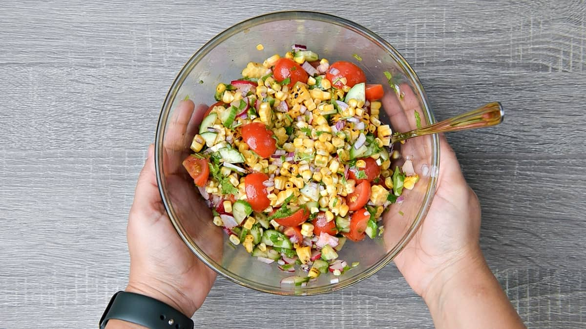 hands holding mixing bowl after tossing summer corn salad together