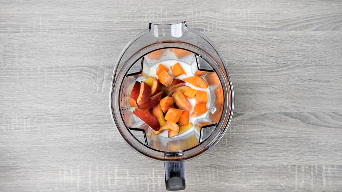 overhead shot of peach smoothie ingredients in a blender pitcher