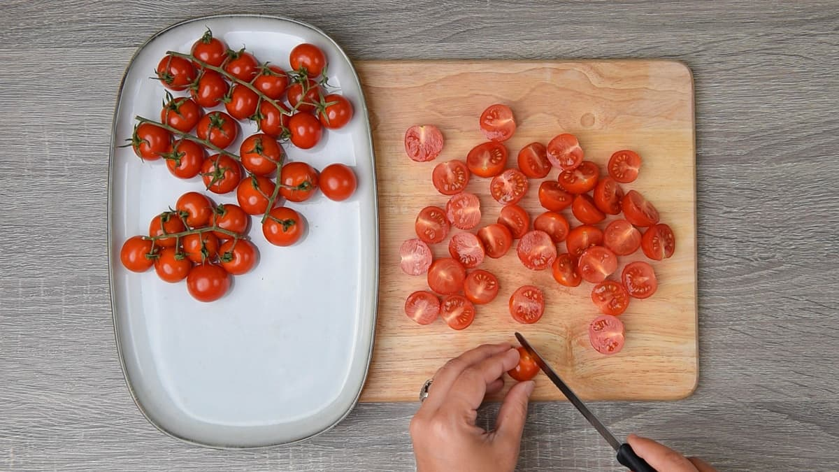hands slicing roughly half of the cherry tomatoes on a wooden cutting board