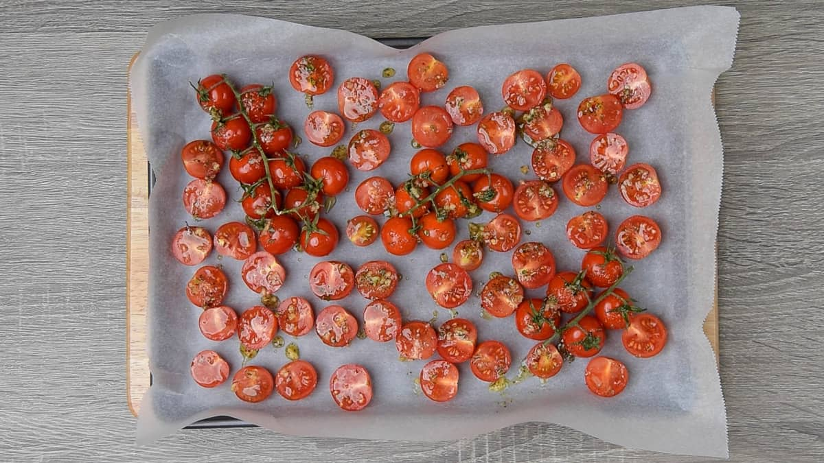 cherry tomatoes on a parchment lined baking sheet and drizzled with oil mixture