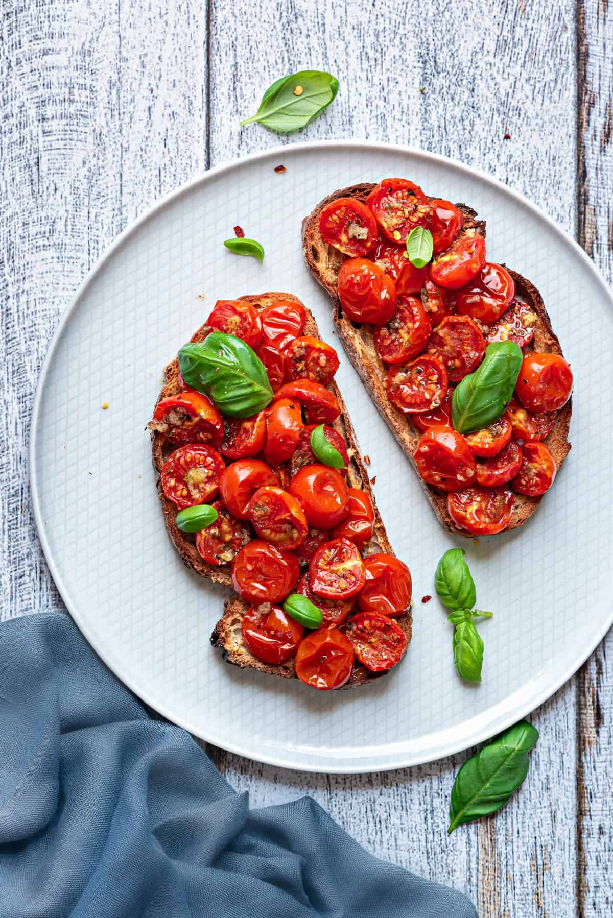 roasted cherry tomatoes on two pieces of toast and garnished with fresh basil leaves