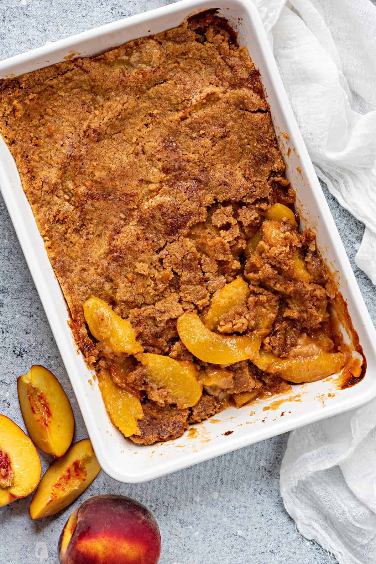 flat lay shot of white casserole dish of baked homemade peach cobbler on a grey table