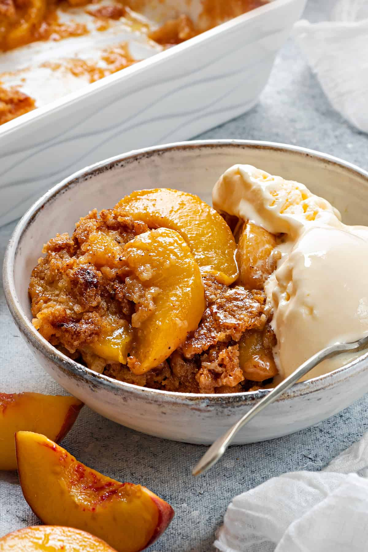 close up shot of peach cobbler in a bowl with ice cream, highlighting the texture of the juicy peaches and the crispy topping