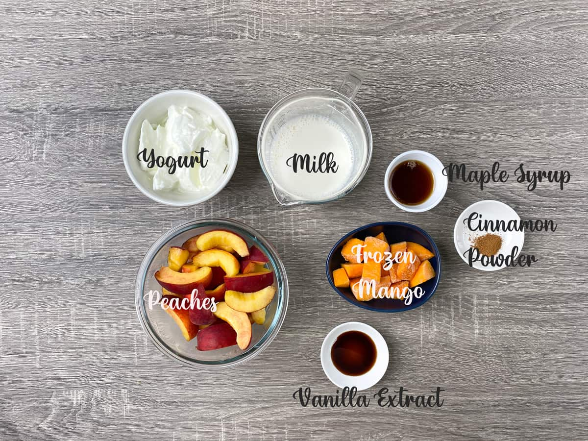 ingredients for mango peach smoothie measured out into bowls and laid on a table
