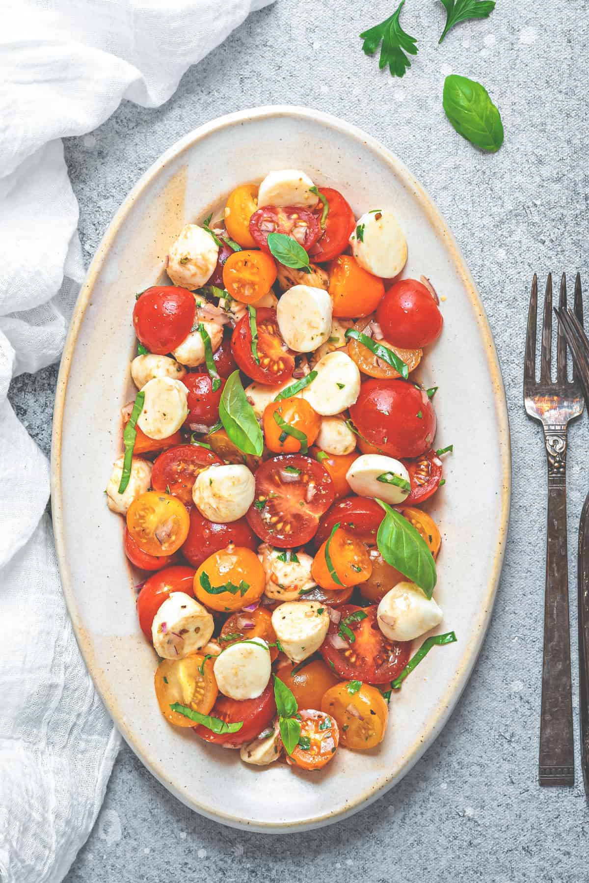 oblong neutral colored serving plate filled with tomato mozzarella salad and garnished with fresh basil