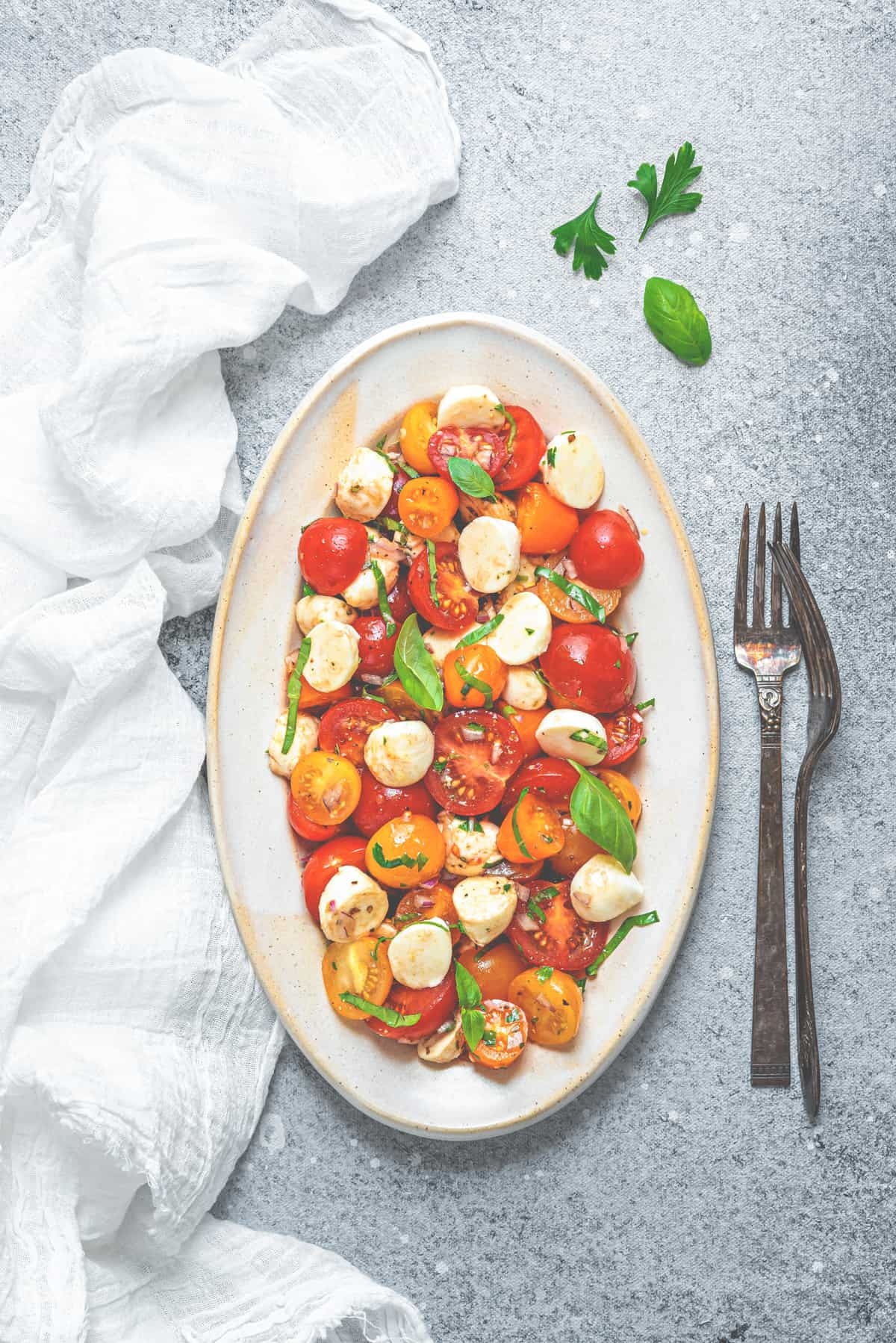 overhead shot of tomato and mozzarella salad on a large serving plate next to silver forks