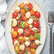 Oval serving plate filled with fresh tomato mozzarella salad and garnished with fresh basil