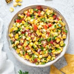 overhead shot of a white earthenware serving bowl filled with roasted corn salsa