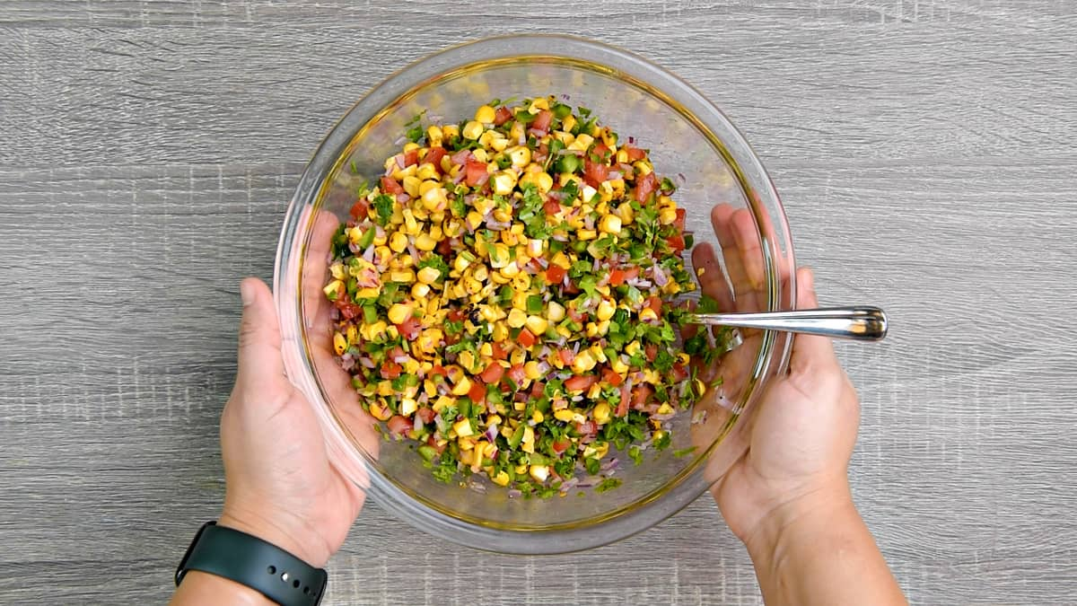 hands holding mixing bowl after tossing corn salsa together