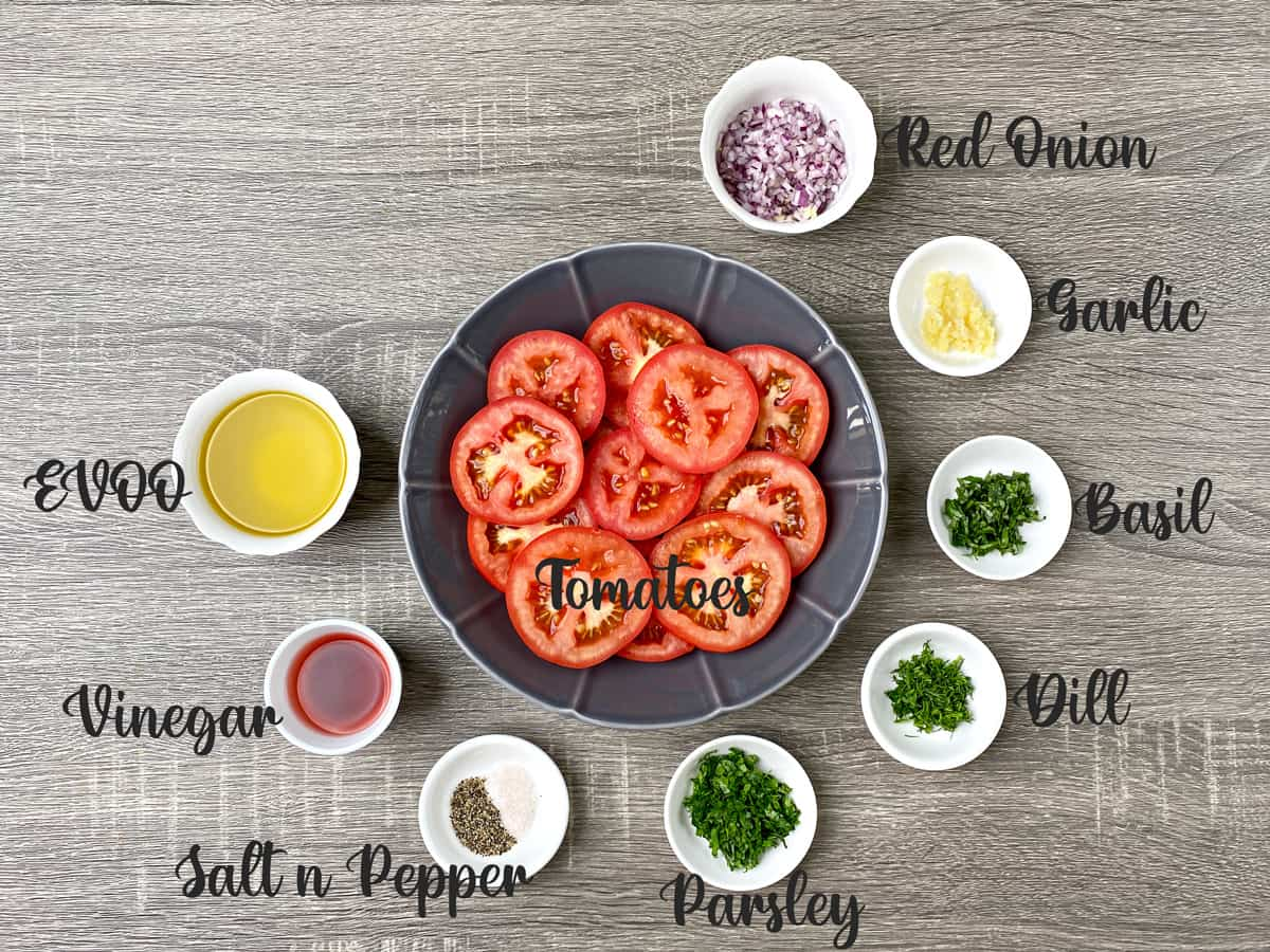 Ingredients for marinating the tomatoes placed in bowls and kept on grey table