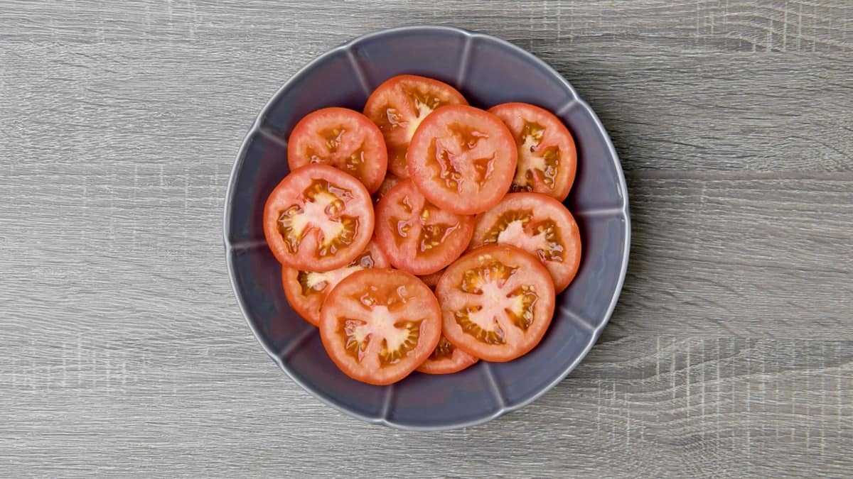 sliced beefsteak tomatoes arranged in grey shallow dish