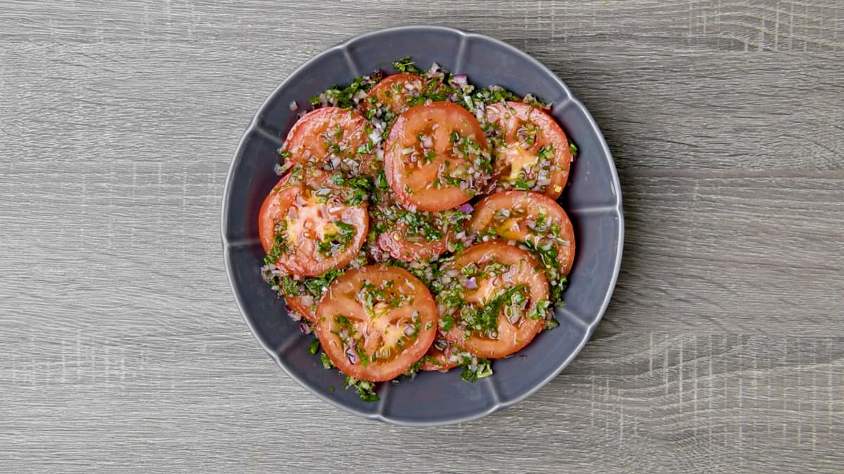 herbed marinade poured over sliced tomatoes