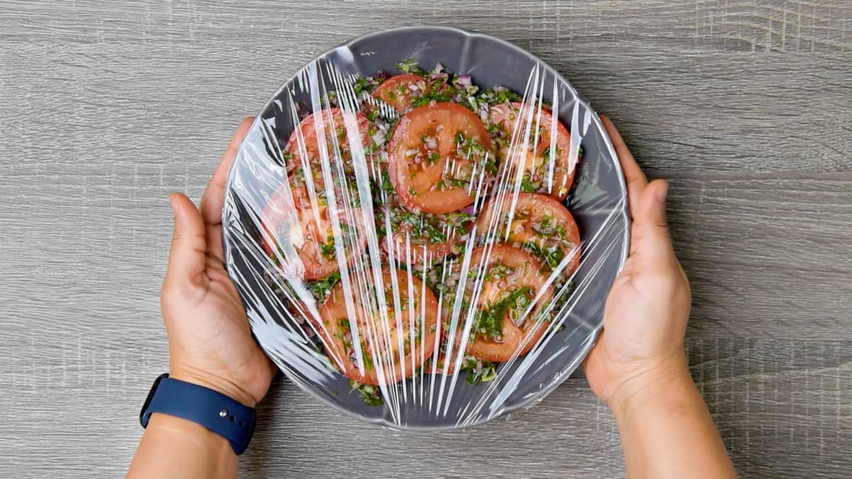 two hands holding plastic wrapped grey dish filled with marinated tomatoes