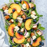 a rectangular serving platter of peach arugula and burrata salad with red onions, chicken and blueberries