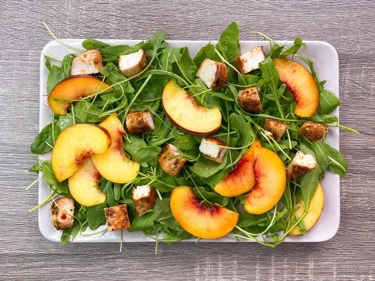 arugula, chicken and peaches artfully arranged on a rectangular serving platter