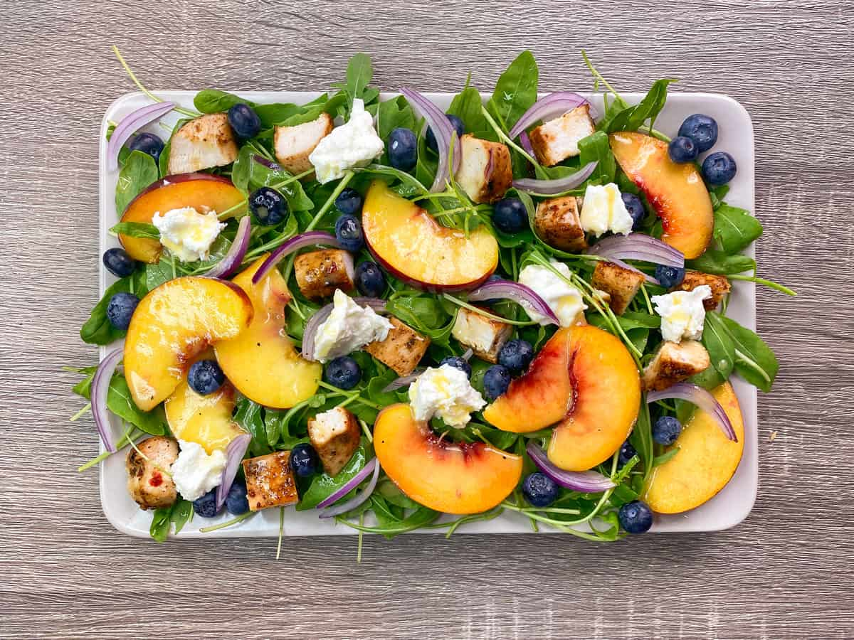 overhead shot of peach arugula salad after drizzling on the dressing and adding the burrata, red onion and berries