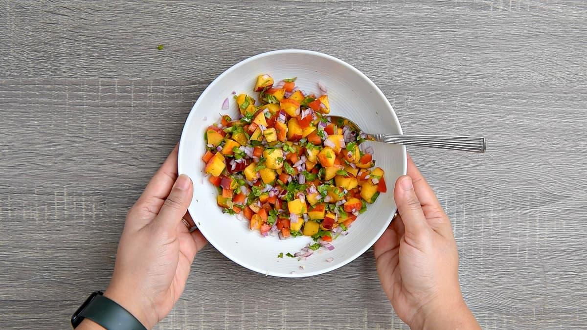 hands holding mixing bowl after stirring salsa ingredients together