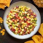 overhead shot of glazed earthenware bowl filled with fresh pineapple salsa