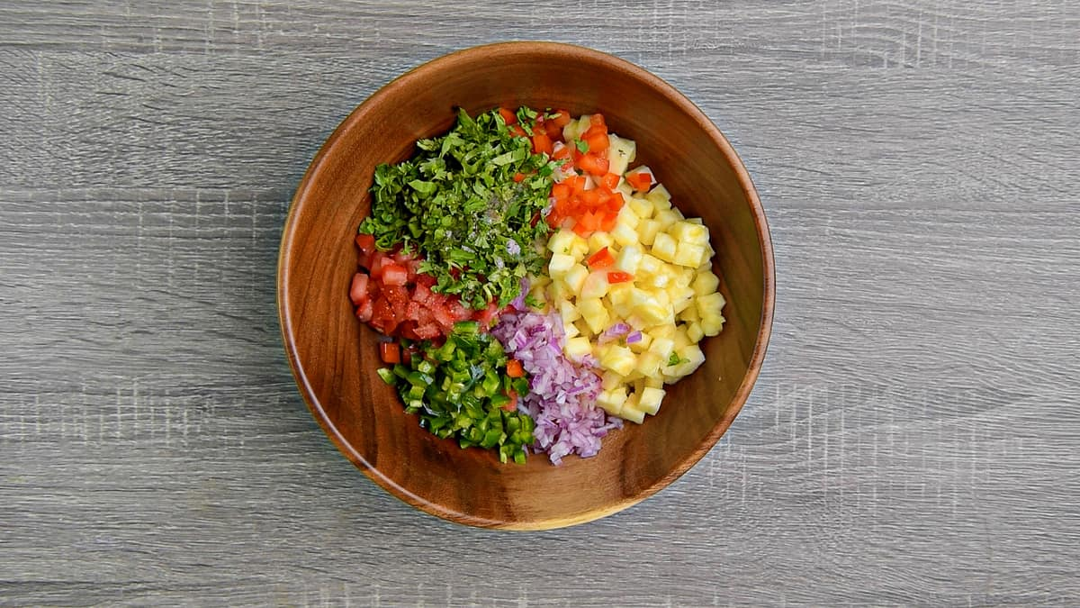 all pineapple salsa ingredients added to wooden salad bowl