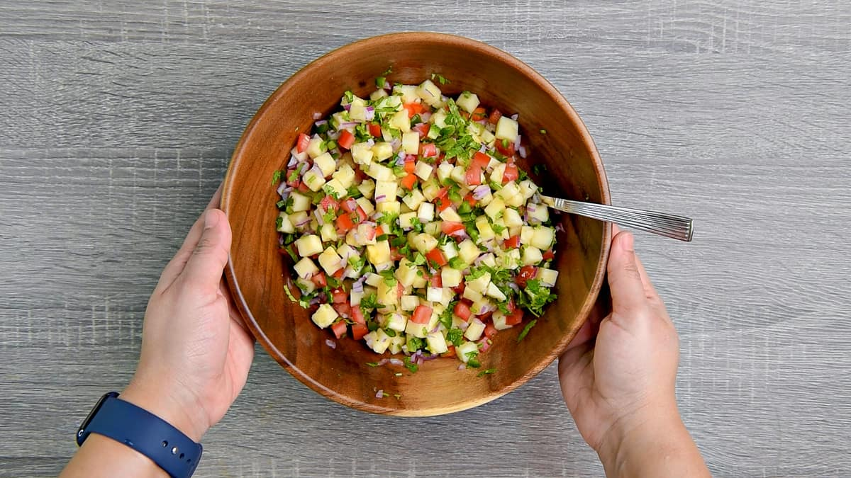 hands holding wooden mixing bowl after stirring pineapple salsa together