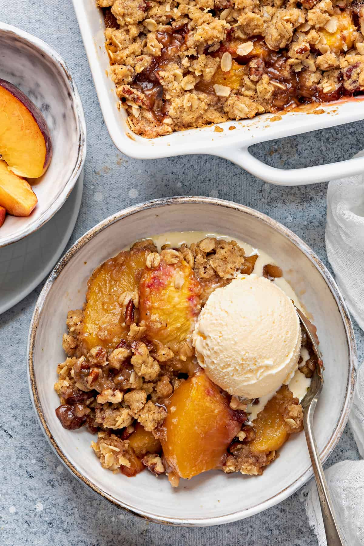 bowl of peach crisp topped with a scoop of vanilla ice cream